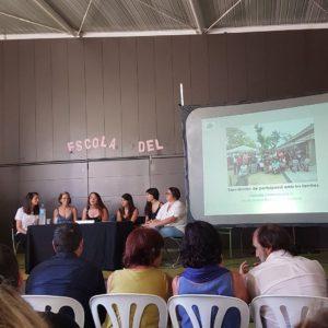 Personal educatiu i famílies de la Granota presenten les seves experiències a Connexions 0-6. A la pantalla, una imatge del jardí de l'escola