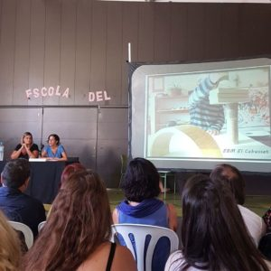 Vanessa i Maria presentant l'experiència d'El Cabusset a Connexions 06. A la pantalla un infant de Cabusset fent una construcció amb peces de fusta