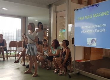 Equip educatiu de Mag Maginet exposant el seu projecte amb presentació sobre pissarra blanca