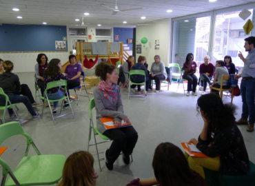 Educadores en petits grups en una sala escoltant el formador